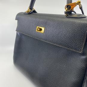 Sælger denne flotte Hermes Kelly 32 Sort Togo i kalveskind fra Hermès Vintage med et håndtag på toppen, en indvendig lynlåslomme, en aftagelig skulderrem og taskefødder.   Kommer kun som taske-only og hængelåsen mangler. Du får kvittering fra os, som garanterer ægtheden og 2 års reklamationret.