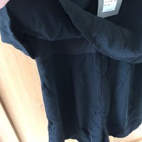 Ærmeløs playsuit løstsiddende med blonder og stropper, lynlås i ryggen.