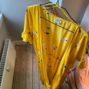Elegant og smuk slå-om kjole fra Saint Tropez i str. L. Åben fortil, og lang bagtil. Har en fin flæse ned langs siden. Anvendelig til alle sæsoner, da både bare ben, strømpebukser og jeans ser fedt ud til.