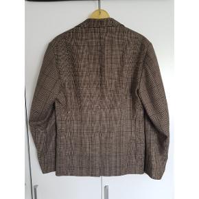 Flot efterårs blazer i rigtig god kvalitet. Brun med tern og orange indvendig.   Den er originalt til mænd, men jeg har brugt den oversize. Jeg bruger normalt medium i blazere.   100% uld.