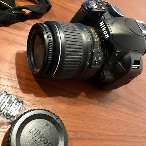 """Nikon D3100 spejlreflekskamera med linse, taske, oplader og rem.   - 14,2 megapixels - Guide-indstilling - Optagelse med fuld 1080p-HD video - 3"""" skærm - 11 punkts AF-system"""