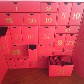 Julekalender i blank og mat rød med guldstriber og guldtal. Kalenderen er med låger, der kan åbnes, og lukker med magnetisk lukning. H:36,5, B: 33, D:16. Kun brugt 1 måned, stadig super flot. N.B. TOM!