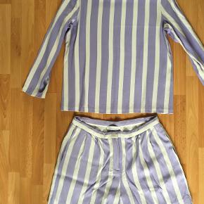 Så lækker sæt bluse og shorts med striber i hvid/lilla. Den har kun været på en eneste gang, men der er kommet en lille bitte hul ved armhulen, som overhovedet ikke kan ses.