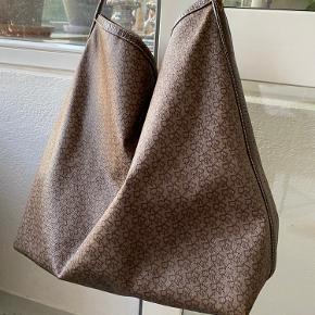 """Rigtig fin """"pose"""" DKNY skuldertaske. Tasken er brugt og det har sat sig sine spor på taske. Tasken fejler ellers intet!   Lukkes ved magnet og har et lille side rum inde i tasken med lynlås.   Taksen har en del år på bagen og kvittering haves derfor ikke.   Ny pris 1200 kr."""