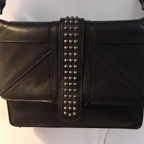 Marc Ellis taske i sort læder / skind med nitter, justerbar skulderrem og magnetlukning. Består indvendigt af to rum, lynlåsrum og to mindre rum til feks mobil. Mål ca: B 26 x H 20 x D 6. Rigtig lækker - er som ny og næsten ikke brugt!