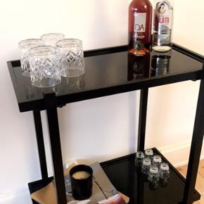 Lækkert bord fra H. Skjalm P. Bordet med små hjul er perfekt til barbord med flasker og glas.  Rullebordet har bordplader i sort spejl og stel i sort jern. Under et år gammelt. Ingen skader til glas eller stel.  Nypris: 2500