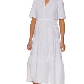 Nyd livet i denne romantiske, afslappede bomuldskjole. Med en åben hals med flæser, lagdelt underdel og T-shirt body kan du nemt style denne kjole til både hverdag og fest. Den har en løs pasform, der giver den et bohemeinspireret look. Materiale: 100 % bomuld. Mål str. 32: bryst 47cm, talje 40cm, hofte 50cm, længde 118cm, ærmelængde 26cm.