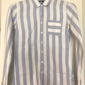 Den yndigste stribede skjorte fra Tommy Hilfiger med flere finurlige detaljer. Brugt få gange.