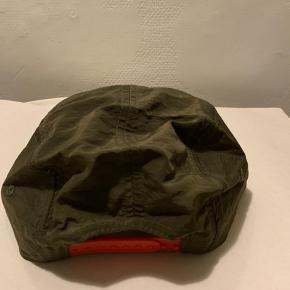 Grøn (Army / Mili grøn) unisex cap / kasket fra Urban Outfitters i str. Onesize. Aldrig brugt og med mærke/tag. Ny pris 175,- Der er rødt '1992' logo foran og rød regulerbar rem bagpå. Materialet er let, tyndt, blødt, så tilpasser sig hovedfacon. Virker let vind / vandafvisende ift materiale Pris r fast! Hvis brevpost via postnord er Porto 20,-