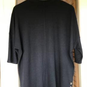 Mørkeblå og enkel bluse i blød kvalitet fra mærket My True Me Tom Tailor i str. 46 (3XL). Delvist løstsiddende model. Høj hals med kant og rund udskæring. Syning ned midt for både fortil og på ryggen. 3/4 lange ærmer. Nederst til venstre ses 3 plastknapper, som giver en ekstra fin detalje. Delvist strækbart materiale.  Materiale: 65% polyester, 35% viskose. L: 65 cm. Bryst: 69 cm (fra ærmegab til ærmegab). Talje: 60 cm (x med 2 for omkreds). Stand: Næsten som ny. Kun brugt 1-3 gange. Købspris: 280 kr. Ingen bon.