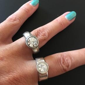 """Othmar """"sølv"""" fingerring med stor simili-sten Indvendig mål 1,7 cm Bredde 0,8 cm 100 DKK  Anden """"sølvfarvet"""" ring med stor simili-sten (med brugsspor) Indvendig mål 1,8 cm Bredde 0,6 cm 50 DKK  Begge ringe 135 DKK"""