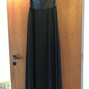 Lang stropløs kjole. Med gummi i kanten på indersiden, så kjolen nemt holdes oppe. Inderskørtet går til midt på låret mens yderskørtet går til ankellængde alt efter højde.  Aldrig brugt, kun prøvet en enkelt gang