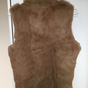 Super fed vintage pelsvest i ægte kaninskind i figursyet model med høj hals, rå kanter og lynlås. Vesten er uforet og man kan derved se den fine patchwork læder inderside når vesten står åben. Kan både bruges indenfor over en bluse eller udenfor oven en strik eller let jakke. Passer str. 36 / S. 100% ægte pels. Kom med et bud.   Varen befinder sig i 9520 Skørping. Sender med DAO.  Se også min øvrige annoncer. Jeg sælger tøj, sko og accessories. Pt er min shop fuld af vintagekup, high street fund og mærkevarer i mange forskellige str. Kig forbi og spøg endelig!!