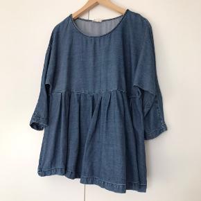 Fineste bluse/tunika i denim stof. Brystmål: 110 cm Længde fra skulder og ned: 70 cm Næsten som ny. Dog lille hul (foto 3).  Derfor sat som god, men brugt😊