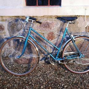 Sjælden retro cykel fra Puch I ekstremt god stand sælges.  Cyklen er fra 79 og kører upåklageligt. Alle dele er originale, samt lædersæde, godkendt Basta lås og dynamo både for og bag.  Cyklen har været opbevaret i opvarmet kælder i +20 år. Derfor den virkelig gode stand. Perfekt cykel til at skille sig ud blandt mængden på en skøn sommerdag.  Cyklen er nedsat med 1000 kr.   - Kode til låsen medfølger.  - Mulighed for levering.