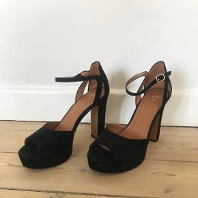 Sorte hæle fra H&M i størrelse 39. Enkle hvide streger på en ene sko men ses næsten ikke. Kun brugt 1 gang til galla (derfor sliden under skoen), ellers i meget fin stand.Hælen er 10 cm.  Kan afhentes i Søborg eller sendes på købers regning