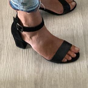 Superfin let sandal. Ruskind/skind. Elastisk i spænde der gør, at den sidder super godt på foden, uden at stramme.  Hælhøjde 7 cm