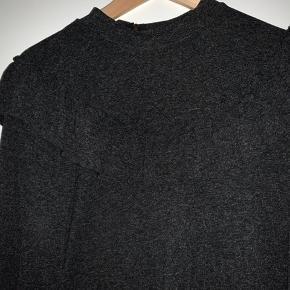 Sælger den søde mørkegrå bluse med lille flæse kant foran og lynlås i nakken! Brugt 4 gange i meget pæn stand. Køberen betaler portoen!