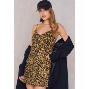"""Den pæneste leopard sommer kjole i str M fra mærket """"Motel"""" med fine sorte knapper og stropper, købt på NA-KD.com for ca. 200 kr. husker jeg det som.  Rigtig fin mellem længde og let,  lækkert materiale, faktisk super blødt. Aldrig brugt, normal i størrelsen, dog vil den også være fin til en S/36 hvis man gerne vil have den skal være lidt """"oversize"""".  Hvis den skal sendes, betaler køber fragt.   Mvh Betina Thy"""