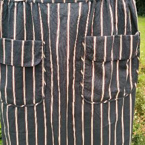 Masai nederdel str. M (sort bundfarve) - elastik i taljen - 2 store lommer samt et læg for og bag der falder blødt  Længde: 80 cm  Mat: 69% cotton 31% polyester  Hoftemål (målt nederst på lommen 58x2 cm eller 116 cm.