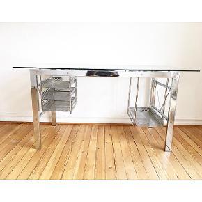 Flot computer/skrivebord i metal med glasplade. Hylderne kan skrues af efter behov.  Rigtig flot og med god plads. Bredde: 150cm Dybde: 70cm Højde: 75cm  Computerhylden måler: Højde: 45cm Dybde: 45cm Bredde: 25cm  Fra røgfrit hjem