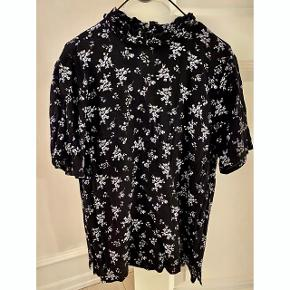 Sort t-shirt med blomster. Lukkes i nakken med knappen. Jeg tager ikke billeder af den på.