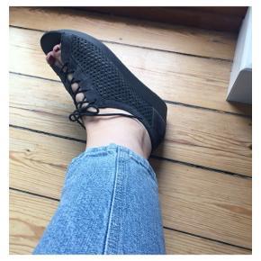 Høje sandaler med snørrebånd. De er lavet i en form for sort, lidt gennemsigtigt net.  Sender gerne med DAO :)