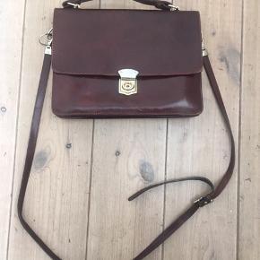 Flot retro lædertaske i brun. Fin stand. Lidt slid indvendig, men giver tasken en flot patina. Mange rum. Mål: bredde: 30 cm, højde 23 cm, dybde 8 cm. Remmen er 120 cm