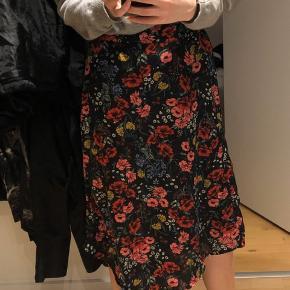 Sort nederdel med blomster, og asymmetrisk snit Elastik i taljen og passer derfor også fint en str s