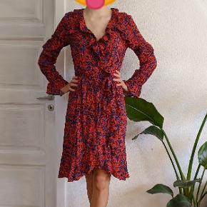 Rød mønstret og blomstret kjole med flæser fra H&M. Har bindebånd i taljen. Aldrig brugt