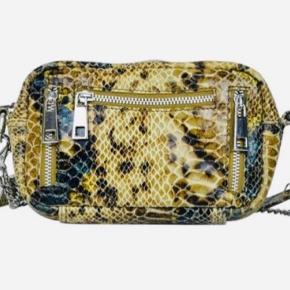 Lækker helt ny Nunoo taske i snake olivengrøn.  Ca. 17 x 14 x 7 cm.  En skulderrem i læder samt en tilsvarende i metal Model Brenda. Materiale: læder.  Aldrig brugt.  Fast pris.