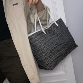 """Fendi vintage shopper!   Fendi Zucca vintage i grå/hvid i god stand. Tasken har lidt slid på hank. Tasken har ikke store skrammer på yderside eller interiør. 100% ægte. Skuldertaskens hanke er hvide, og en smule knækkede i læderet. Det kan være en mac 13"""" i tasken, hvor der stadig er plads til en masse andet. Perfekt til taske til skole/studie.  Jeg har ikke kvittering, da den er vintage.   Mindsteprisen er 3500kr.  Jeg svarer ikke på spørgsmål omkring ægtheden og jeg sælger ikke til under mindsteprisen."""