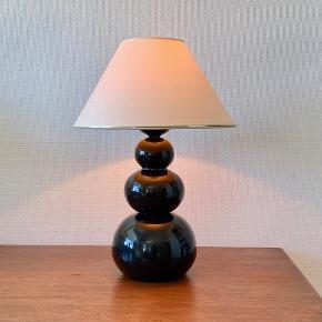 En smuk og moderne bordlampe med et enkelt udseende, der passer ind i de fleste indretninger. Lampens fod har en flot sort farve, og lampen spreder et godt, hyggeligt lys.  Lampen tændes og trinreguleres blot ved at lægge en hånd på den nederste del. Højde: 39 cm Diameter: 16,5 cm Prisen er ekskl skærm
