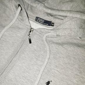 Vintage Ralph Lauren hoodie med lynlås i lysegrå farve. Har haft den i godt og vel 10 år, men har aldrig fået den brugt, og kan sku ikke passe den længere. Kan ikke finde billeder eller pris på den fra dengang, men mener ny prisen ligger på omkring 600,-.  Stretch i bund og ved ærmet. Så god som ny. Giv et bud!