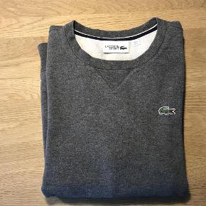 Varetype: Sweatshirt Størrelse: M Farve: Mørkegrå Oprindelig købspris: 700 kr.  Super smart Lacoste sweatshirt i mørkegrå. Det er en voksen str. S men har i dette tilfælde passet en dreng på 13/14 år.  Jeg har ligeledes en mørkeblå Levis sweatshirt , en lys grå Bennetton, en blå blazer samt en Stone Island dunjakke til salg.