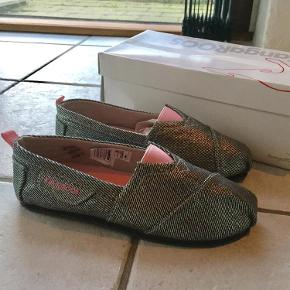 Varetype: Sko Farve: Sølv - Lyserrød Oprindelig købspris: 300 kr.  Super fin og smart sko fra Kangaroos, som både kan bruges som sommersko eller hjemmesko. Skoen er lige til at smutte i og lavet i sølvfarvet kanvas med rosa farvet elastik ved vristen. Blød sål indvendigt og gummisåler under bunden.  Modellen hedder Sam   Stadig i kasse- aldrig brugt
