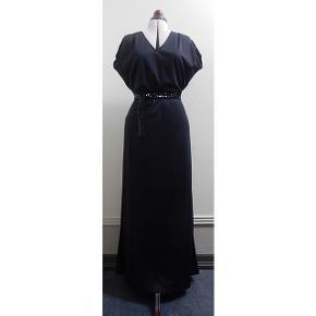 Sort vintage maxi kjole fra 1070erne. Fra det Svenske mærke Deha, se billede. Materialet er kunsttof og er elastisk med viskose for i nederdelen. Bæltet kan reguleres efter størrelse. Kjolen fremstår som ubrugt. Mål: Bryst max 96 cm. Talje kan reguleres mellem 72 - 82 cm da der er elastik og bælte. Hofte max 102 cm. Længde 146 cm.