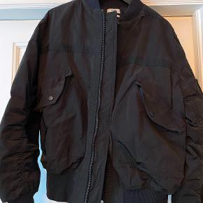 CMMN SWDN → Bomber jacket / bomber jakke → Det svenske haute couture tøjmærke der de seneste år har fået flere honorable bemærkninger i de Parisiske modekonferencer og modeshows. Jakken er købt i high-end butikken Storm Copenhagen.   Bomberjakken fra CMMN SWDN sidder lidt cropped, stramt i håndled og liv, og resterende af jakken er ret løst. Den skaber et ret sejt look da den sidder tight, men stadig er puffy.  Derudover fremkommer jakken realitet regntæt(det skal ikke være skybrud), og holder også godt på vind, storm, blæst (hvad det nu bliver til). Det kan tælles på to hænder hvor mange gange jakken er brugt (9/10)  Jakken har en perfekt pasform, og af virkelig høj kvalitet. Prisen afspejler kvaliteten og designprocessen bag jakken — det er tydeligt, at jakken vil holde utroligt længe og ikke falme, og blive træt at se på.  Hvis i har et hav af spørgsmål, eller bare et enkelt, skal i endelig ikke holde jer tilbage. Om det er flere billeder, brugsstand, pakketilbud med flere af mine varer, el. andet — jeg er her for jer.