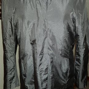 Let jakke i let sølvskinnende stof. Skjult lukning. Der står ikke materiale samt størrelse i jakken. Ginen den er på, er en str 38