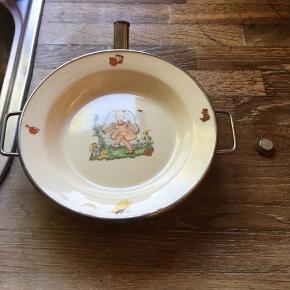 Barnetalerken til varmt vand hældes i trakten den er muligvis tysk produceret, den er 23 i diameter med håndtag og 5cm høj en fin lille ting der både kan anvendes og til pynt