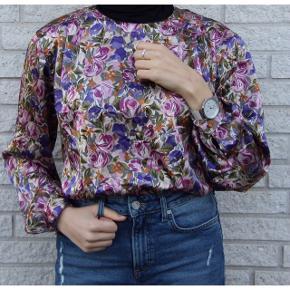 Skjorte fra 1980'erne med de flotteste farver og motiver. Skjorten har en rigtig flot blank overflade, og har medium skulderpuder. Skjorten vil passe en str 32-40, og kan bruges til enhver lejlighed. Kan kombineres med alt, og et bælte i midten vil pifte skjorten op.