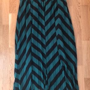 Plisseret nederdel med sort underdel, der giver den et let look og delvis gennemsigtig nederst.   Et fejlkøb - har muligvis endda bonnen:-)