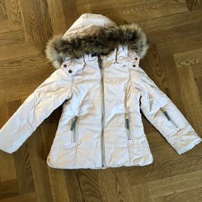 Lækker varm vinterjakke i sart rosa farve. Nem at vaske og fremstår uden pletter el huller og har ingen særlige brugstegn. Fremstår som ny. Aftagelig ægte pels samt aftagelig hætte. Vindstop i selve jakken.