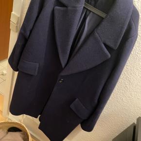 Lang overgangsjakke i mørkeblå. Jakken er oversize