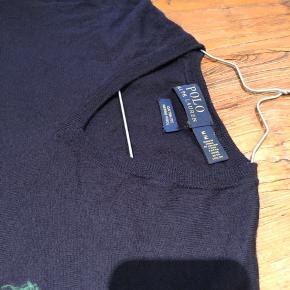 Sælger denne Polo Ralph Lauren cardigan med v-neck i merino uld, da den er for lille. Er brugt 7-8 gange.  Den er købt i USA (sidste år), hvilket betyder at den fitter lidt anderledes end størrelserne herhjemme. Jeg vil vurdere den til at være ca. tilsvarende en lille medium custom fit.  Kvittering haves desværre ikke, men jeg står 100% inde for ægteheden på trøjen. Farven er navy med en grøn hest på brystet. Der er et lille hul i nakken på trøjen (se billedet), derfor den lave pris.  Skriv endelig, hvis du ønsker at se flere eller bedre billeder. Kan afhentes i Hellerup eller sendes på købers regning.  Tjek evt. mine andre annoncer, hvor jeg bl.a. har mere fra Ralph Lauren. Respekter venligst min pris, da den er fast :-)