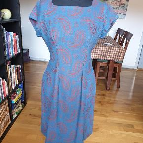 Vintage håndsyet kjole fra 60'erne.  Jeg er desværre ikke sikker på hvad materiale den er lavet af, men det virker til at være en uldblanding. Den er lidt løs i syningen ved lynlåsen bagpå, men det kan nemt ordnes, da der ikke er tale om stræk af selve stoffet, men i selve syningen. Man er velkommen til at komme og prøve den.