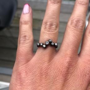 Smuk sort rhodineret/oxideret ring i sterlingsølv fra Frk Lisberg.   Ringen har 7 funklende zikoner og passer en størrelse 52(54).   Brugt få gange.  Nypris: 1099 kr.  Sælges for: 599 kr.   Afhentes i Kbh k. Eller sendes med post - Porto 30 kr. (Ikke forsikret).