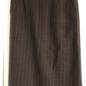 Retro nederdel i uld. Er brun/sort/rød/karrygul i farverne. Har remme til bælte og lommer.