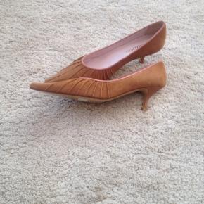 Skoene er fra Isabell i Lyngby. Helt nye og ubrugte. De er lavet i det blødeste ruskind og med ægte læder sål. Flot detalje med lyse kant og den guldfarvet sål. Ny pris kr. 799,-.