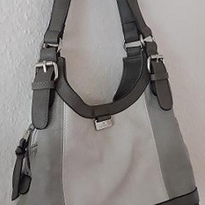 Tom Tailor taske i 4 farver nuancer . Mørkegrå, mellem grå, lysegrå og helt lysegrå . Taske har tre rum . Midterste rum med lynlås. Lille  indvendig lomme  og en udvendig lomme med lynlås.  Lukkes både med magnet knap og lynlås. Brugt en gang et par timer. Fin stand som ny